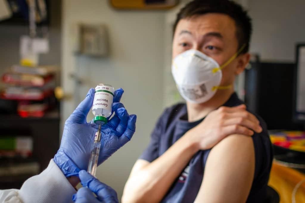covid precaution - man taking corona vaccine